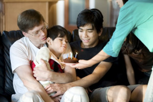 Disabled little boy blowing candles